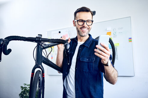 Smiling businessman carrying bicycle in office looking at smartphone - BSZF01061