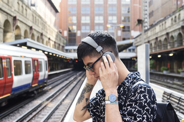 Young man listening music with headphones, standing on station - IGGF00872