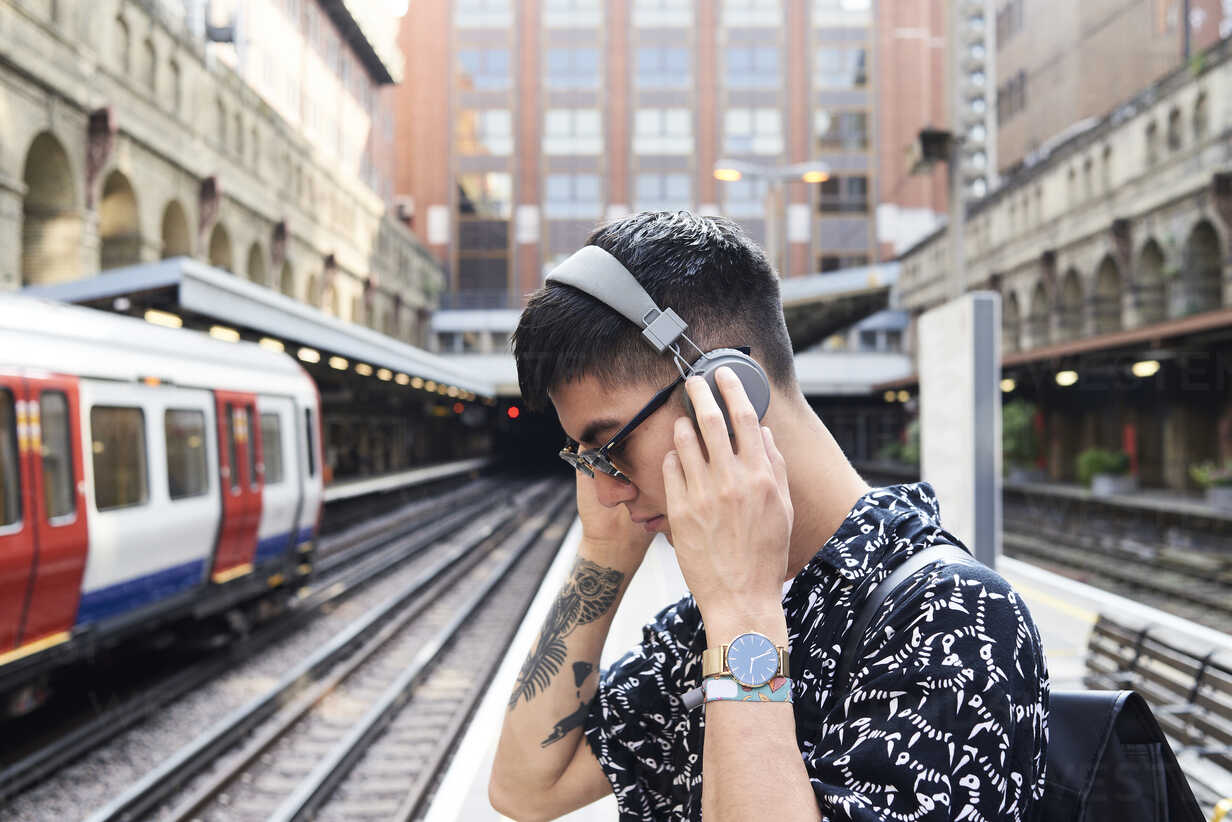 Young man listening music with headphones, standing on station - IGGF00872 - Ivan Gener/Westend61
