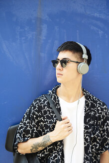 Young man listening music with headphones against blue wall - IGGF00875