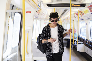 Young man listening music with headphones inside train - IGGF00878
