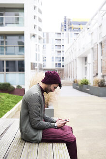 Side view of bearded guy in purple hat and clothes browsing mobile phone sitting on bench in modern district. - IGGF00887