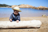 Spain, Menorca, toddler playing with deadwood on the beach - IGGF00896
