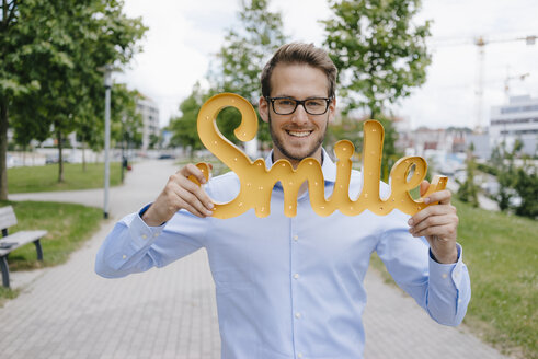 Young businessman holding smile sign - KNSF05570