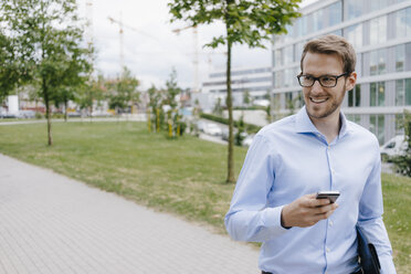 Young businessman walking in park, using smartphone - KNSF05573