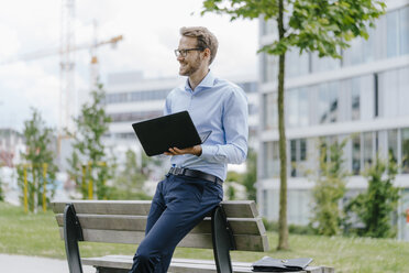 Young businessman sitting on park bench, using laptop - KNSF05579