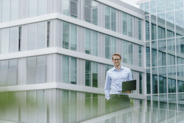 Young businessman standing in front of modern office building, using laptop - KNSF05582