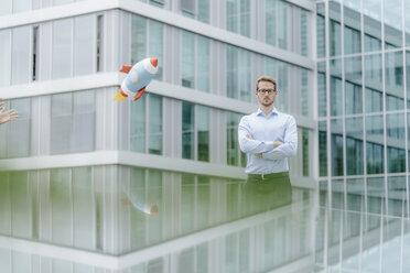 Young businessman standing in front of modern office building, watching toy rocket - KNSF05585
