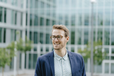 Young businessman standing in front of modern office building, smiling - KNSF05588