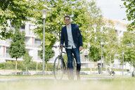 Young businessman in park, leaning on his bicycle - KNSF05594