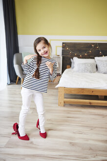 Little girl dressing up, wearing mother's red high heels - ABIF01175