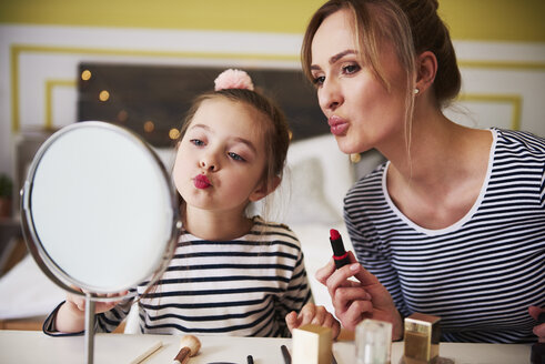 Mother and daughter applying make up together, using lipstick - ABIF01196