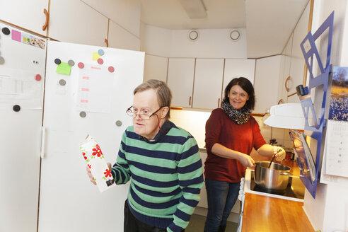 Mentally challenged senior man helping caregiver preparing food in kitchen - ASTF04903