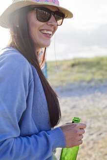 Smiling young woman holding beer bottle at beach - ASTF04930