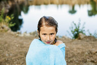 Portrait of cute girl wrapped in towel standing at lakeshore - ASTF05008