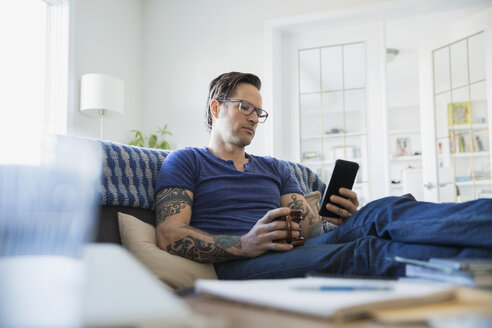 Man tattoos and coffee texting in living room - HEROF24546