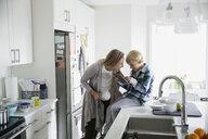 Mother smiling at son using digital tablet kitchen - HEROF24555