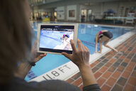 Female coach with digital tablet camera photographing girl swimmer preparing to jump into swimming pool - HEROF24672