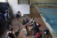 Female coach coaching stroke to swimming team at poolside practice - HEROF24678