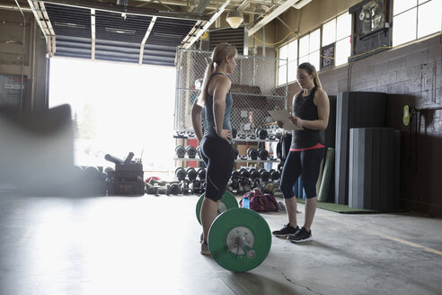 Female personal trainer with clipboard training woman weightlifting at barbell in gym - HEROF24684