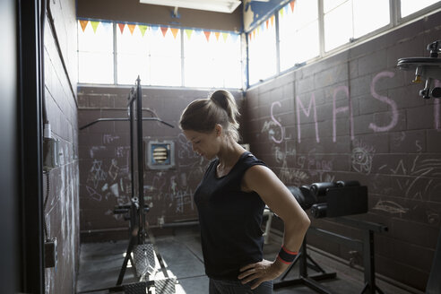 Fit woman weightlifting in gritty gym - HEROF24687