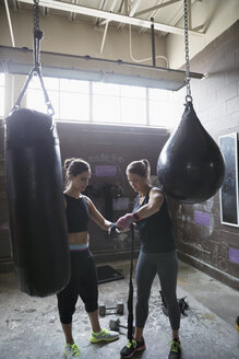 Fit women wrapping wrists behind punching bags in gritty gym - HEROF24696