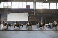 Focused, strong women exercising, doing planks in a row in exercise class - HEROF24702