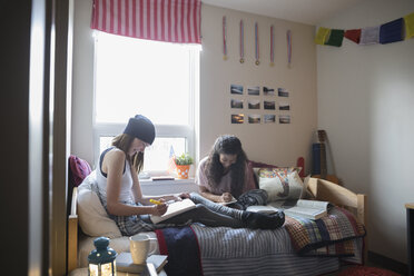 Female college students studying on bed in dorm room - HEROF24711