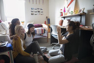 Female college student friends posing for photograph in dorm room - HEROF24729