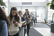 Female college student texting with cell phone in queue - HEROF24750
