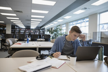 Focused male college student studying, researching at laptop in library - HEROF24753
