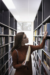 Female college student looking at books on bookshelves in library - HEROF24765