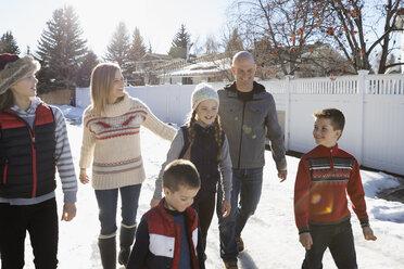 Family walking on sunny snowy street - HEROF24780