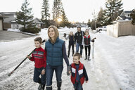 Family walking with ice hockey sticks on snowy road - HEROF24789