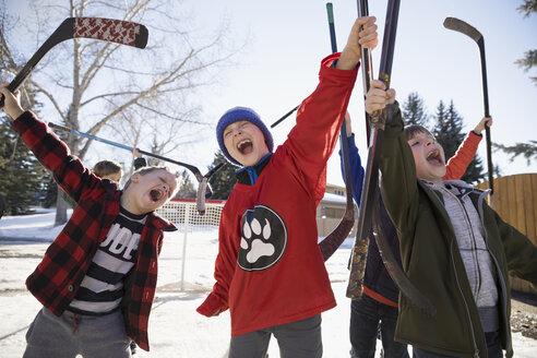 Enthusiastic boys cheering, playing ice hockey in sunny driveway - HEROF24792