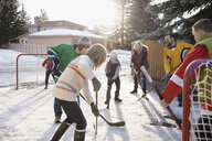 Families playing ice hockey in sunny, snowy driveway - HEROF24795