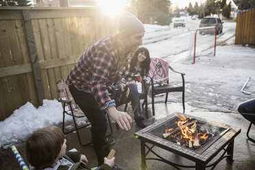 Family roasting marshmallows at fire pit in snowy driveway - HEROF24798