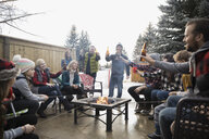 Families, neighbors toasting beer bottles at fire pit in winter driveway - HEROF24801