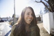 Enthusiastic brunette woman smiling on sunny road - HEROF24804