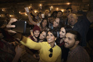 Enthusiastic friends taking selfie with camera phone at party - HEROF24810