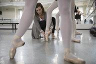 Female instructor adjusting foot of ballet dancer in dance studio - HEROF24840