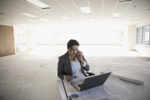 Female architect working at laptop in empty, unfinished open plan office - HEROF24849