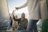Friends opening bottle of champagne on sunny sailboat - HEROF24918