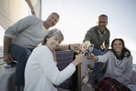 Friends toasting champagne flutes on sunny sailboat - HEROF24921