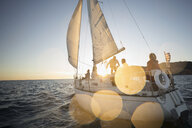 Friends sailing on sunset sailboat - HEROF24924