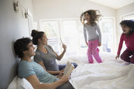 Family relaxing and playing on bed in morning - HEROF24933