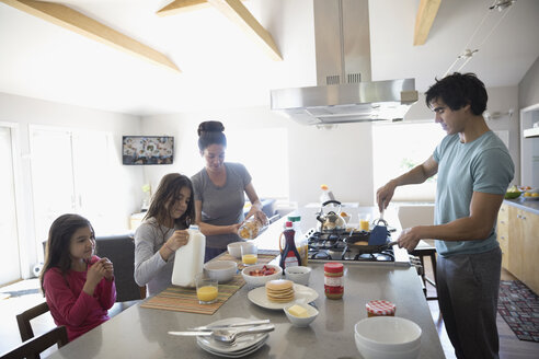 Family cooking and eating breakfast in kitchen - HEROF24936