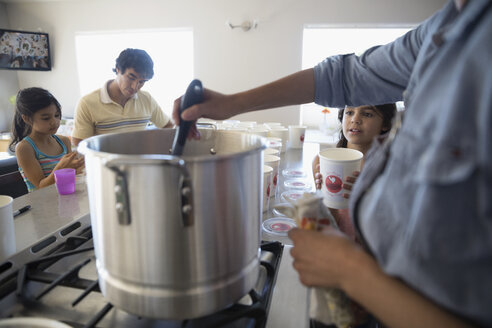 Family cooking at stock pot in kitchen - HEROF24942