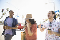 Friends laughing and walking with coffee on sunny California street - HEROF24945