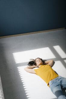 Woman lying on floor, relaxing in the sunlight - KNSF05630